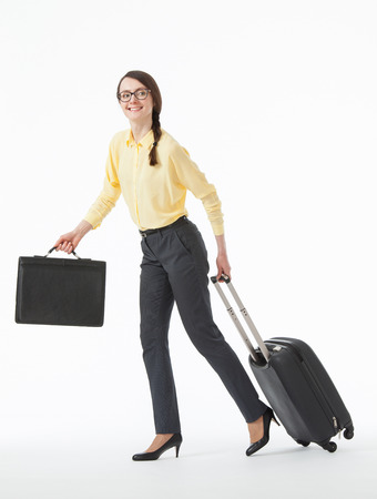 Vrij jonge vrouw die met een koffer, witte achtergrond gaat