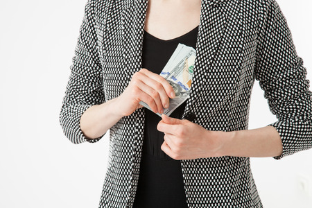 corruptible: Unrecognizable businesswoman hiding money, closeup shot
