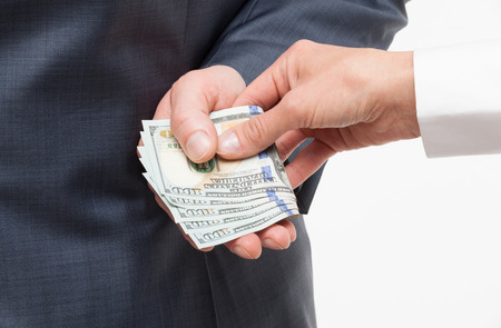 venal: Businessman giving a bribe, neutral background Stock Photo
