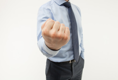 govern: Unrecognizable businessman showing a strong fist, white background Stock Photo