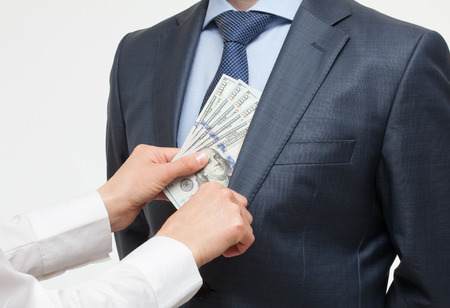 corruptible: Giving a bribe into a pocket - closeup shot Stock Photo