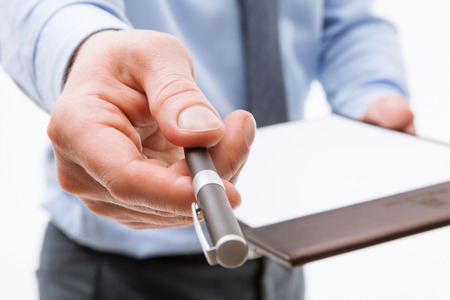 dignified: Businessman holding a clipboard with empty sheet of paper and proposing a pen, white background Stock Photo