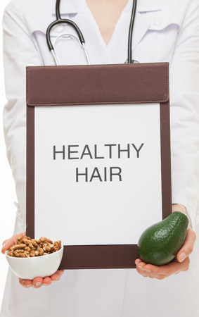 circassian: Doctor holding a clipboard with text Healthy hair, avocado and circassian walnuts - healthy hair concept