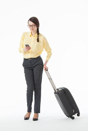 Mooie jonge vrouw met een mobiele telefoon en een koffer, witte achtergrond