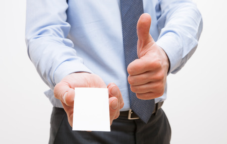 unrecognizable: Unrecognizable businessman showing  visiting and thumb up sign, white background