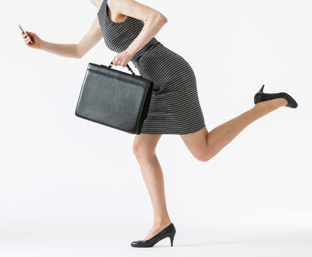 hasten: Unrecognizable businesswoman running and holding her cellphone and a briefcase, white background