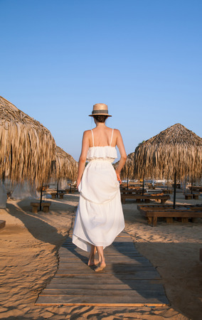 sundress: Young woman in a white sundress and hat  walking by the beacn