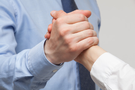 conflict: Businessmens hands demonstrating a gesture of a strife or solidarity, white background