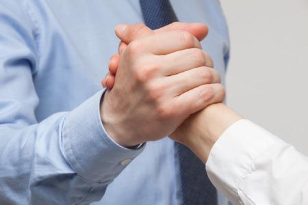conflict: Las manos de los hombres de negocios que muestran un gesto de una contienda o la solidaridad, el fondo blanco Foto de archivo
