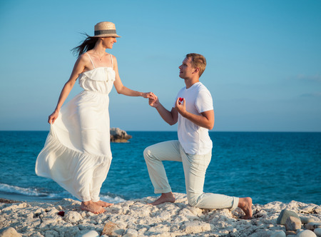 Young man proposing marriage to happy young woman, sea background