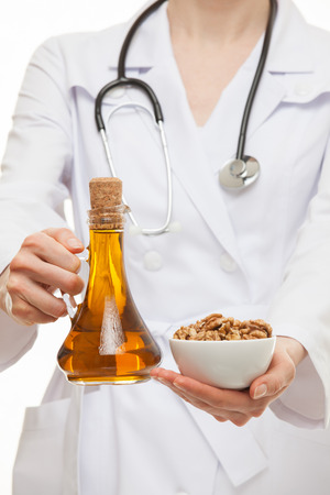 circassian: Doctor holding circassian walnuts and olive oil - healthy lifestyle concept Stock Photo