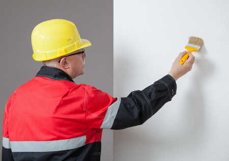 colourer: Painter in an yellow helmet painting a wall, rear view Stock Photo