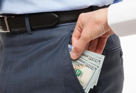 venal: Giving a bribe into a pocket - closeup shot Stock Photo