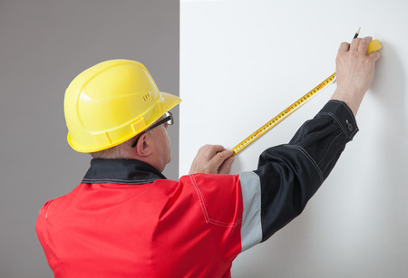 yellow hard hat: Man in the yellow hard hat determining the distance Stock Photo