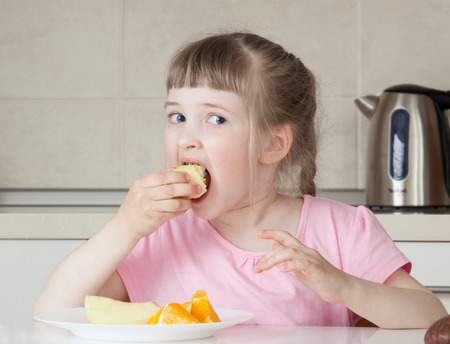 upgrowth: Happy little girl eating tasty food at home