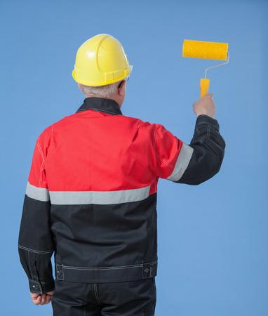 colourer: Painter in an yellow helmet holding a roller, rear view