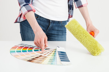 colourer: Unrecognizable woman examining palette and holding a roller, white background