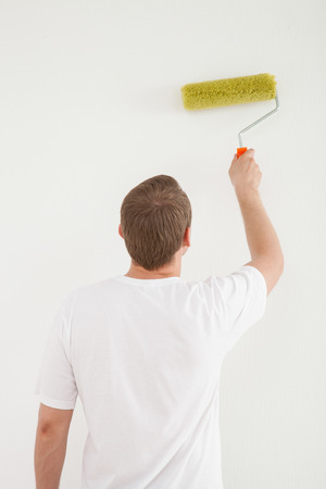 colourer: Young man painting a white wall with a roller Stock Photo