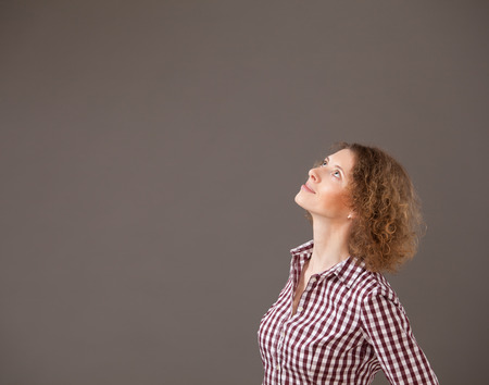 unworried: Portrait of a young woman looking up, gray background