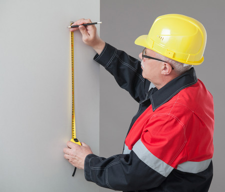 superintendent: Man in the yellow hard hat determining the distance Stock Photo