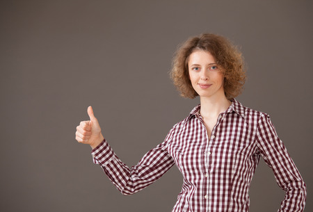 unworried: Portrait of a young woman showing thumb up gesture, gray background Stock Photo