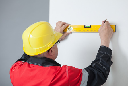 determine: Builder turning back and holding a level and a pen, gray background