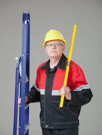 superintendent: Builder holding a ladder and a level, gray background