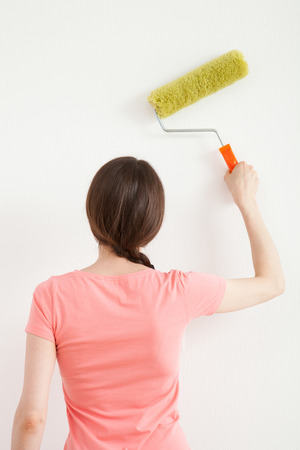 colourer: Young woman painting a white wall - new home concept