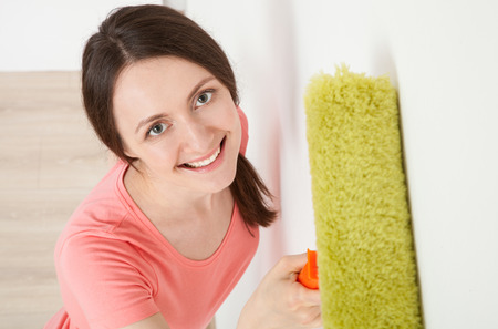 colourer: Smiling young woman painting a white wall - new home concept
