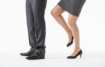 contradiction: Businesswoman kicking a businessman, white background Stock Photo