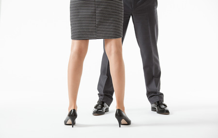 conflicting: Unrecognizable business peoples legs in conflicting pose , white background Stock Photo