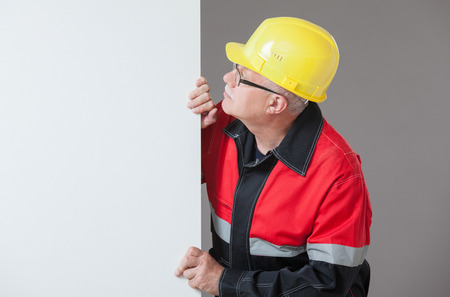 superintendent: Mature builder peeping  out from behind the white wall, gray background