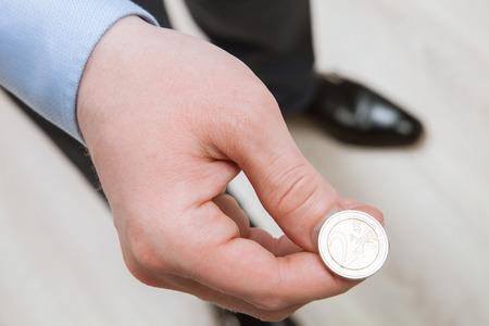 사업가 던지기 동전 - 총 근접 촬영