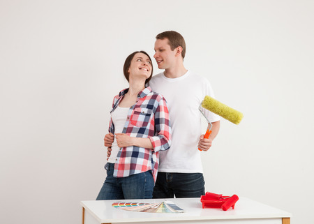 colourer: Happy young couple in a new flat, white background