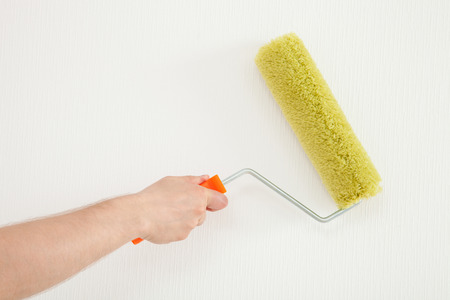 colourer: Male hand holding a roller on wall background Stock Photo