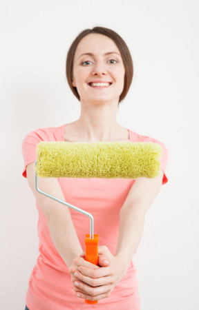colourer: Young woman showing a roller - new home concept Stock Photo