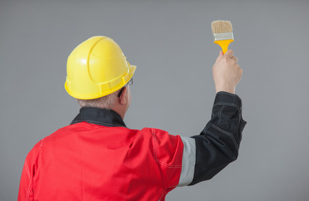 colourer: Painter in an yellow helmet holding a brush, rear view, grey background