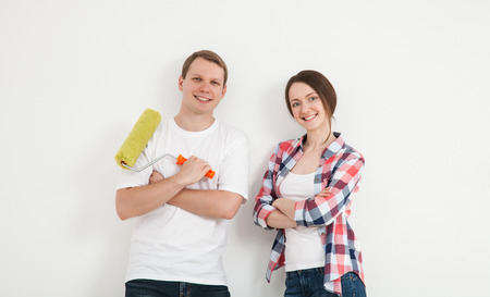 Happy young family repairing a new flat, standing near the wall