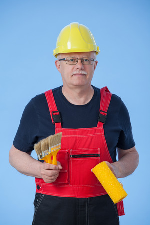 colourer: Painter in an yellow helmet holding three brush and a roller, blue background