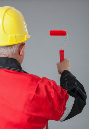 colourer: Painter in an yellow helmet holding a small red roller, rear view