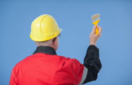 colourer: Painter in an yellow helmet holding a brush, rear view, blue background