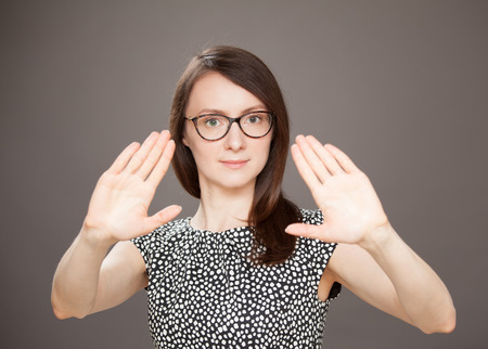 repulsive: Young woman showing repulsive gesture, dark background