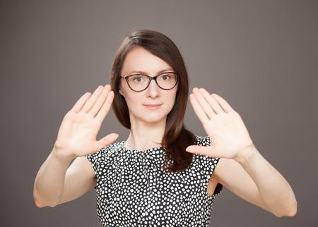 renounce: Young woman showing repulsive gesture, dark background