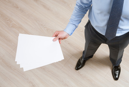 instruction sheet: Unrecognizable businessman holding empty sheets of paper, view from above
