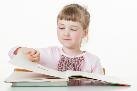 former years: Pretty little girl turning over pages of a book, white background