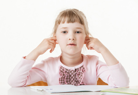 disinclination: Pretty little girl sitting with closed ears at school desk, white background