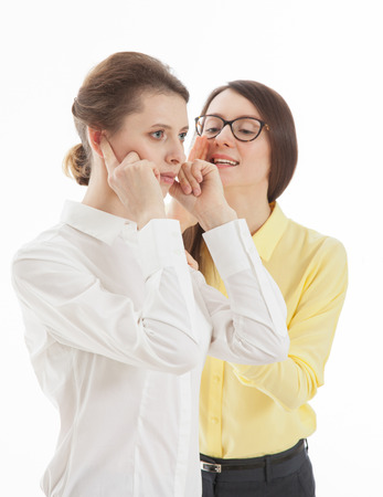 disinclination: Smiling young woman whispering  in colleagues  ear a secret, white background Stock Photo