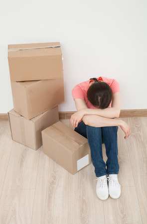 knee bend: Worn young woman sitting on the floor near the pipe of boxes Stock Photo