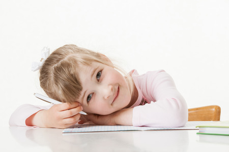 industrious: Happy little school girl learning to write, white background Stock Photo