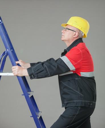 climb job ladder: Builder climbing on a ladder, gray background